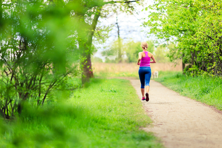 runner: Woman runner running and walking in park, summer nature, exercising in bright forest outdoors