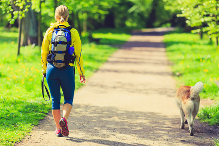 Woman runner running and walking with dog in park, summer nature, exercising in bright forest outdoors Standard-Bild