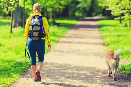 Vrouw running en wandelen met de hond in het park, de zomer de natuur, oefenen in helder bos buiten