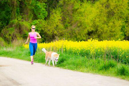 mujer con perro: Corredor de la mujer corriendo con el perro en el parque en la carretera nacional, estilo de vida saludable y la formación ejercicio al aire libre, hacer ejercicio en el ambiente colorido brillante. Concepto de inspiración y motivación.