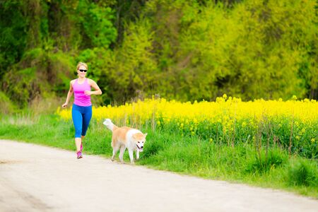 power walking: Woman runner running with dog in park on country road, healthy lifestyle and training working out outdoors, exercising in bright colorful environment. Inspirational and motivational concept. Stock Photo