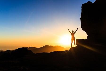 Mujer senderismo éxito silueta escalada en las montañas, la motivación y la inspiración en hermosa puesta de sol y mar. Caminante femenino con los brazos arriba extendidos en cima de la montaña mirando noche hermosa puesta de sol paisaje inspirador.