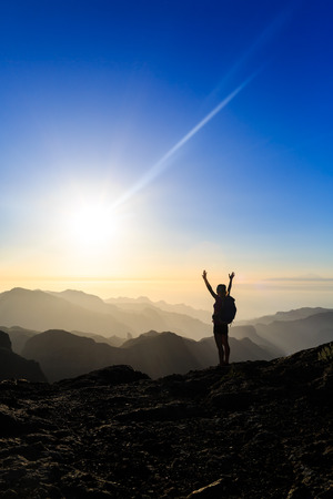 女性成功ハイキング登山山、モチベーションとインスピレーションの美しい夕日と海のシルエット。女性ハイカーを両手を広げて美しい夜日没の感