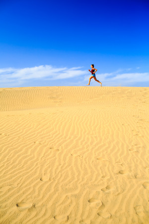 power walking: Young woman running on beautiful inspirational desert dunes on sunny summer day. Beauty female runner jogging and exercising, inspiration and motivation outdoors in nature Gran Canaria, Canary Islands