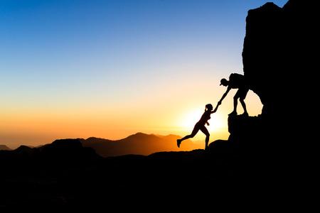 escalando: Pareja de trabajo en equipo mano amiga confianza ayuda silueta en las montañas, puesta del sol. Personas de los escaladores hombre y mujer excursionistas, se ayudan mutuamente en la cima de la montaña, escalar juntos, hermoso paisaje puesta de sol en Gran Canaria Foto de archivo
