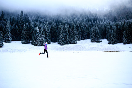 cold woman: Sport, fitness inspiration and motivation. Young happy woman cross country running in mountains on snow, winter day. Female trail runner jogging exercising outdoors.