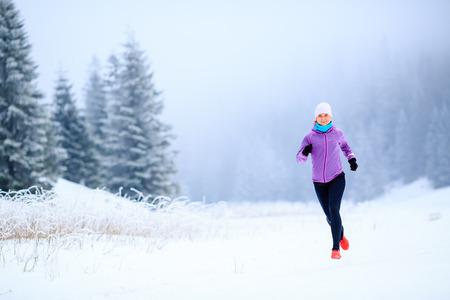 motion: Sport, fitness inspiration och motivation. Ung lycklig kvinna terränglöpning i bergen på snö, vinterdag. Kvinna trail löpare jogging utövar utomhus.