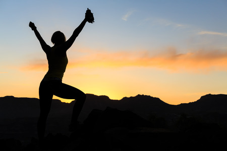 Woman hiking silhouette in mountains, sunset and ocean. Female hiker, climber or trail runner with arms outstretched on mountain top looking at beautiful night sunset inspirational landscape. Stock Photo