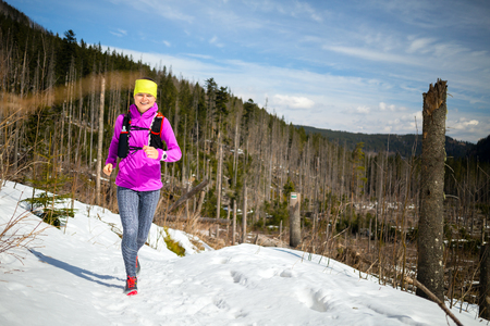 power walking: Happy young woman trail running in mountains on snow in winter sunny day, motivation and inspiration fitness contept landscape. Active runner or hiker power walking outdoors in nature.