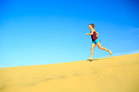 nature beauty: Young woman running on beautiful inspirational desert dunes on sunny summer day. Beauty female runner jogging and exercising outdoors in nature Gran Canaria, Canary Islands