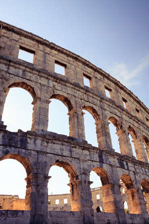 arena: Roman amphitheater arena, theater and coliseum. Classic historical antique building. Tall wall with round arches of an ancient architecture. Popular travel destination of Istria at Adriatic Sea in Pula, Croatia Stock Photo
