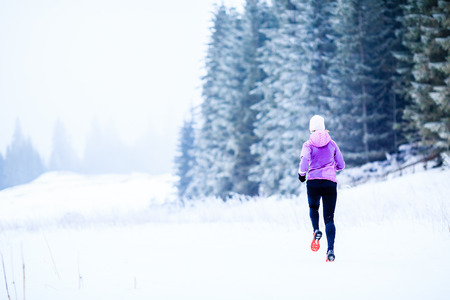 motivation: Sport, fitness inspiration and motivation. Young happy woman cross country running in mountains on snow, winter day. Female trail runner jogging exercising outdoors.