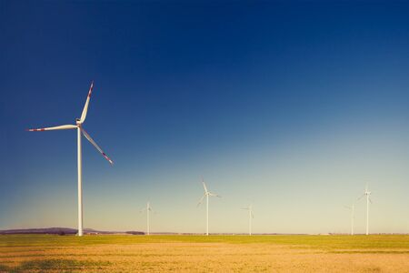 clean energy: Wind turbine farm, alternative energy, electricity power generators on green field. Clean energy on vintage inspirational summer landscape Stock Photo