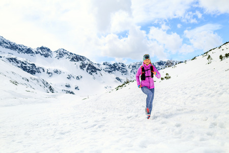 power walking: Happy young woman running in mountains on winter sunny day, motivation and inspiration fitness contept landscape. Active runner or hiker power walking outdoors in nature.