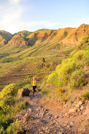 power walking: Young woman running or power walking in mountains on sunset summer day. Beautiful inspirational landscape and female runner jogging exercising outdoors in nature, rocky trail footpath on Gran Canaria Stock Photo