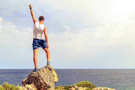 Success achievement climbing, running or hiking accomplish business concept with man celebrating with arms up raised outstretched. Successful hiker, climber or trail runner inspirational landscape