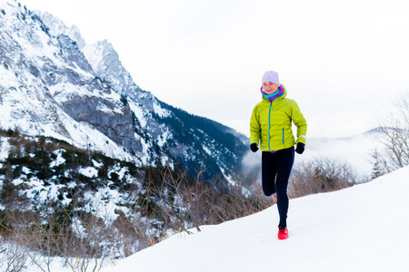 winter sports: Sport, fitness inspiration and motivation. Young happy woman cross country running in mountains on snow, winter day. Female trail runner jogging exercising outdoors.
