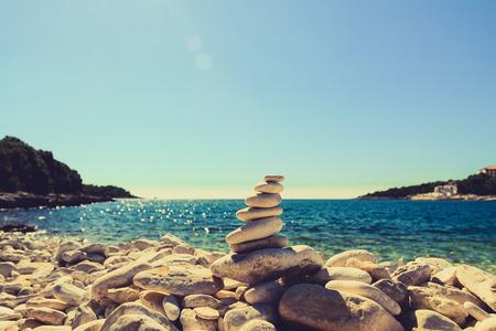 빈티지 해변에서 돌 균형, 영감 여름 풍경입니다. 크로아티아에서 푸른 바다를 통해 안정성 계층 스택. 스파 나 웰빙, 자유와 바위에 안정성 개념입니