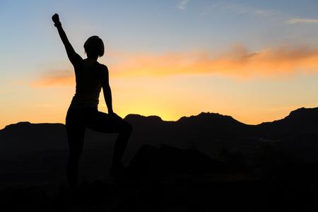 Silueta de la mujer de senderismo en las montañas, puesta de sol y mar. Caminante femenino, escalador o corredor de pista con los brazos extendidos en la cima de la montaña que mira la noche hermosa puesta de sol paisaje inspirador. Foto de archivo - 44396581