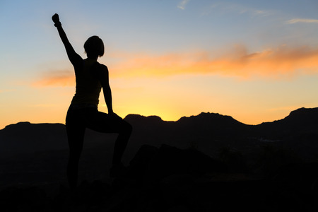 Woman hiking silhouette in mountains, sunset and ocean. Female hiker, climber or trail runner with arms outstretched on mountain top looking at beautiful night sunset inspirational landscape. Banco de Imagens