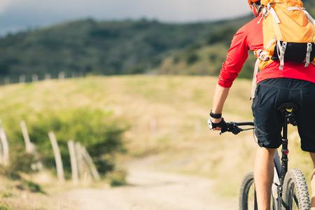 Mountainbiker Reiten auf dem Fahrrad im Sommer, Berge, Landschaft. Mann Radfahren MTB auf ländlichen Landstraße. Sport Fitness-Motivation und Inspiration.