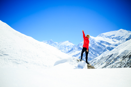 peak: Young happy woman hiker successful on mountain peak summit in winter mountains. Climbing inspiration and motivation, beautiful landscape. Fitness healthy lifestyle outdoors on snow in Himalayas, Nepal. Stock Photo