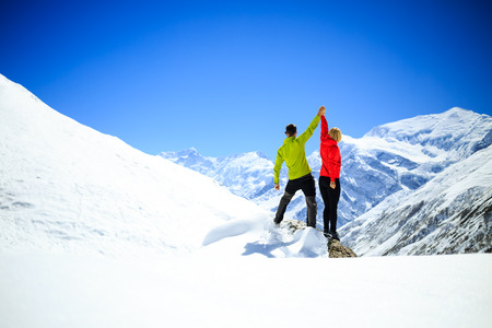 accomplish: Couple hikers man and woman success in winter mountains. Accomplish and climbing motivation in beautiful landscape. Fitness healthy lifestyle outdoors on snow in Himalayas, Nepal. Annapurna range trekking. Stock Photo