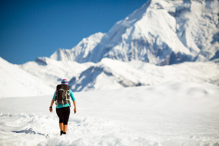 himalayas: Woman hiker walking in beautiful inspirational winter mountains. Trekking and hiking inspiration and motivation in beautiful landscape. Travel and healthy lifestyle outdoors on snow in Himalayas, Nepal. Stock Photo