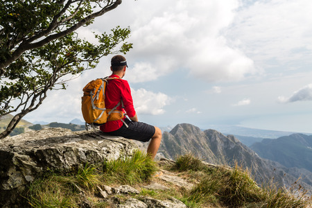 Hiking man, climber or trail runner looking at beautiful view in mountains. Travel in Italy, Europe. Fitness and healthy lifestyle outdoors in fall autumn nature