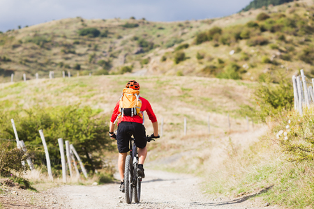 fitness motivation: Mountain biker riding enduro on bike in summer mountains landscape. Man MTB adventure cycling with backpack on rural country road. Sport fitness motivation and inspiration.