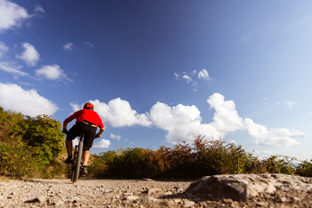 fitness motivation: Mountain biker riding on bike in summer mountains landscape. Man cycling MTB on rural country road. Sport fitness motivation and inspiration.