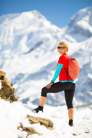 healthy looking: Young happy woman hiker looking at mountain peaks in winter mountains. Hiking and travel inspiration and motivation, beautiful landscape. Fitness healthy lifestyle outdoors on snow in Himalayas, Nepal.
