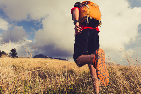 Hiking man or trail runner walking in mountains. Travel in Italy, Europe. Fitness and healthy lifestyle outdoors in fall autumn nature
