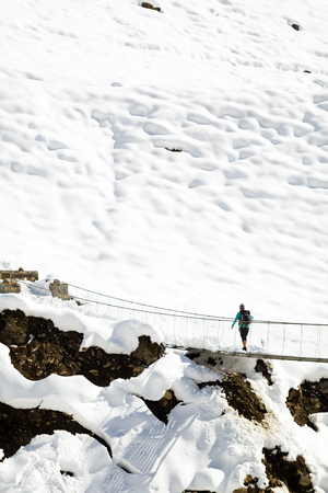hiking: Young woman hiker walking on bridge in beautiful inspirational winter mountains in Himalayas. Hiking inspiration and motivation, beautiful landscape. Adventure outdoors on snow, Nepal.