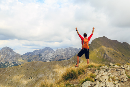arms up: Hiking man and success in mountains. Fitness and healthy lifestyle outdoors in summer nature