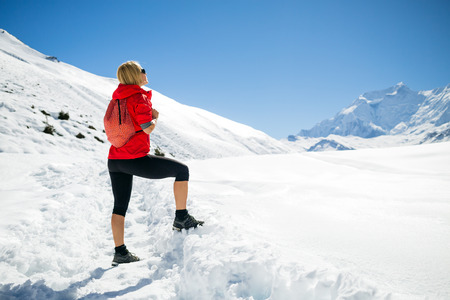 winter woman: Young happy woman hiker looking at mountain peaks in winter mountains. Hiking and travel inspiration and motivation, beautiful landscape. Fitness healthy lifestyle outdoors on snow in Himalayas, Nepal.