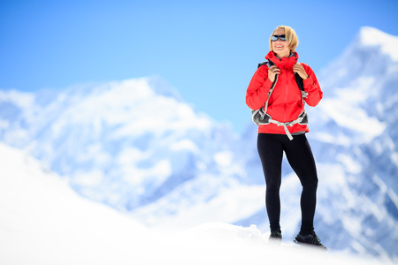 summits: Young happy woman hiker portrait on mountain peak summit in winter mountains. Climbing inspiration and motivation, beautiful landscape. Fitness healthy lifestyle outdoors on snow in Himalayas, Nepal. Annapurna range trekking.