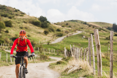 Mountain biker riding on bike in summer mountains landscape. Man cycling MTB enduro on rural country road. Sport fitness motivation and inspiration. Standard-Bild
