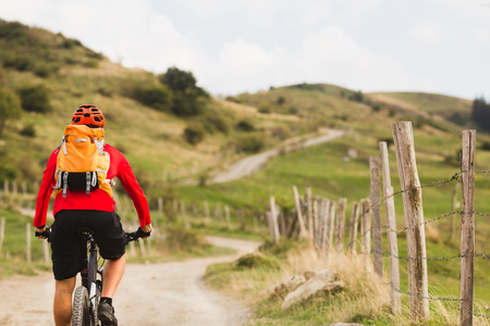 italy landscape: Mountain biker riding on bike in summer mountains landscape. Man cycling MTB on rural country road. Sport fitness motivation and inspiration.