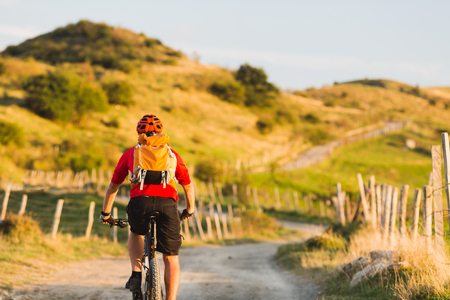 motivation: Bicycle riding enduro adventure in sunset summer mountains landscape. Man cycling MTB on rural country road. Sport fitness motivation and inspiration.