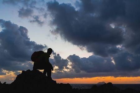 silueta hombre: Hombre caminante sentado lograr silueta mochilero, mirando inspirador océano paisaje isla, concepto de la libertad. Fitness y estilo de vida saludable al aire libre en la playa de Creta, Grecia. Foto de archivo