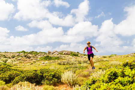 greece: Trail running woman cross country running in inspirational mountain landscape on beautiful day. Training and working out runner jogging and exercising fitness outdoors, rocky footpath on Crete, Greece