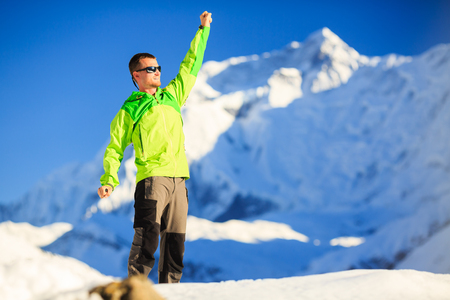 accomplish: Man hiker or climber accomplish in winter mountains, inspiration and motivation achievement business concept.  Success climbing on snow, beautiful inspirational landscape with Annapurna mountain in background.