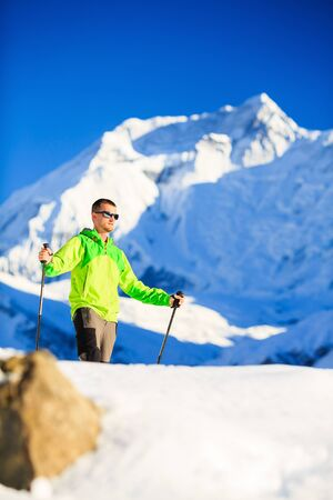 accomplish: Man hiker or climber accomplish in winter mountains, inspiration and motivation achievement business concept.  Success climbing, beautiful inspirational landscape with Annapurna mountain in background. Stock Photo