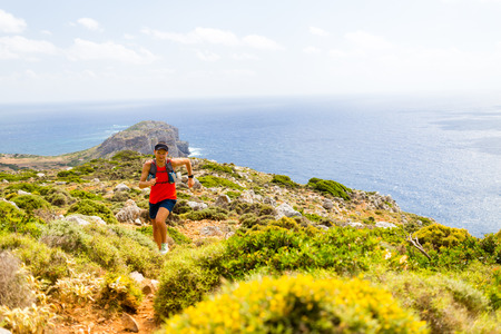 Trail running man, happy cross country runner in mountains on summer beautiful day. Training and working out person jogging and exercising outdoors in nature, rocky footpath on Crete, Greece Stock Photo