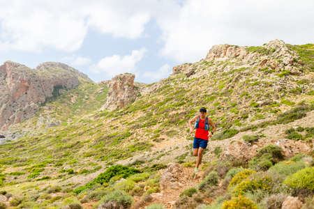ultra: Trail running man, happy cross country runner in inspirational mountains on summer beautiful day. Training and working out person jogging and exercising outdoors in nature, rocky footpath on Crete, Greece Stock Photo