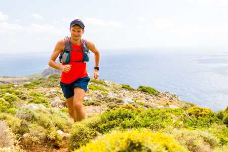 Trail running man, happy cross country runner in inspirational mountains landscape on beautiful day. Training and working out person jogging and exercising outdoors in nature, rocky footpath on Crete, Greece