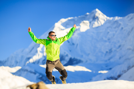 mountain peaks: Man hiker or climber happy ecstatic achievement in winter mountains, inspiration and motivation accomplish business concept.  Success climbing on snow, beautiful inspirational landscape with Annapurna mountain in background.