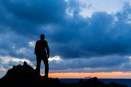 success: Hiking or trail running accomplish silhouette hiker backpacker, man and success in inspirational sunset landscape. Fitness and healthy lifestyle outdoors in summer nature on Crete, Greece. Stock Photo