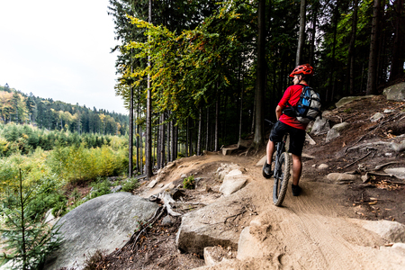 road cycling: Mountain biker riding on bike in autumn inspirational mountains landscape. Man cycling MTB on enduro trail track. Sport fitness motivation and inspiration.